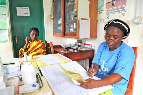 (Right) Ophelia, a certified midwife, records information about Meliere Thahi (left) at the Janzon Clinic in Grand Gedeh County.