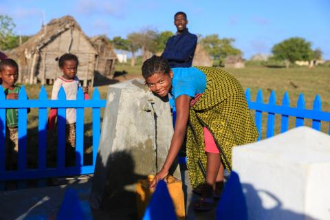 A girl holds a jerry can under a tap, Madagascar