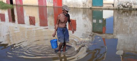 A man carrying a bucket wades through a flooded area in the city of Morondava