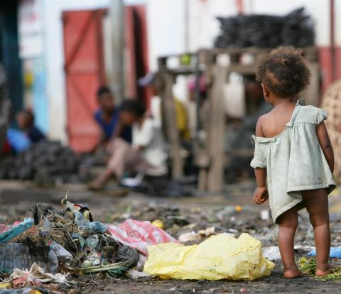 A toddler stands near a pile of debris in Ampefiloha Ambodirano, one of the poorest neighbourhoods in Antananarivo, the capital.
