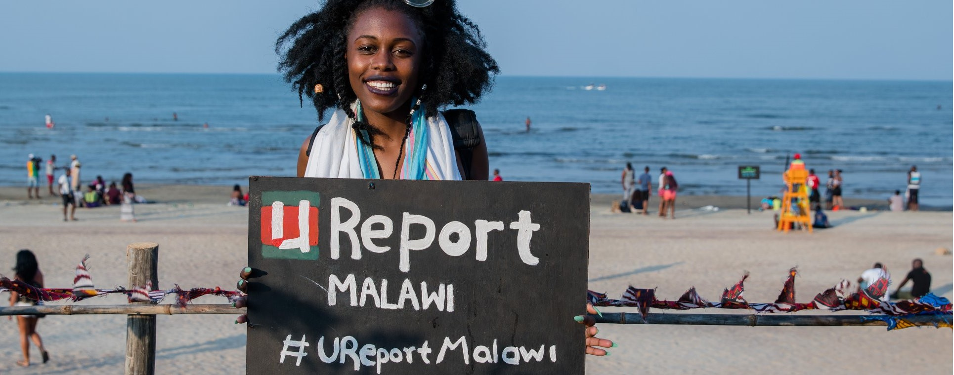 A girl holding a U-Report Placard at Lake of Stars Music Festival