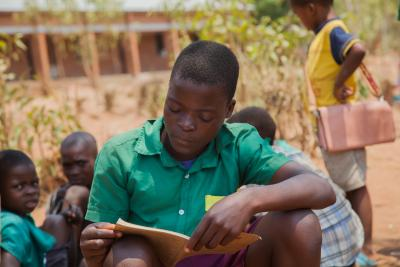 A boy reading notes at Phaloni Primary School in Machinga