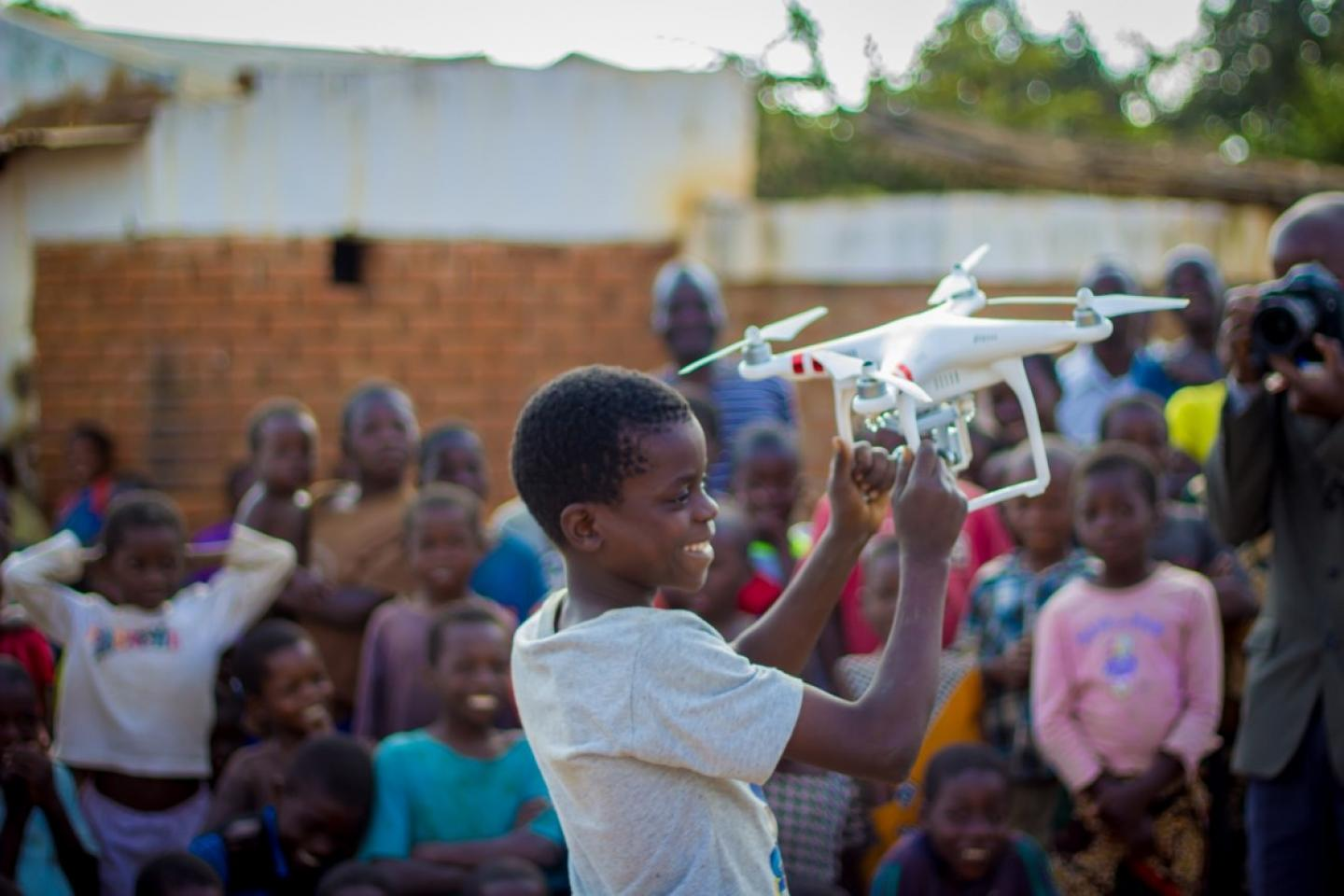 A boy carries a drone at Chisazima village in Kasungu