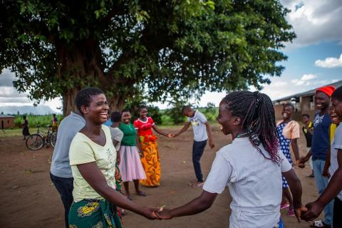 Prisca,16, (yellow T-shirt) the youth group leader and 19-year-old Meria, the adolescent champion (white t-shirt) enjoy a game together during one of their Teen Club meetings