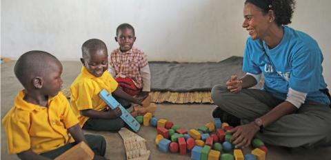A UNICEF staff member plays with children at a CCBC in Blantyre