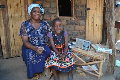Florence and her mom Shillah outside their home. Next to them is the radio Florence uses for her studies.