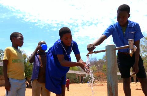 Children using the water tap installed by UNICEF at Nankhwali Primary School