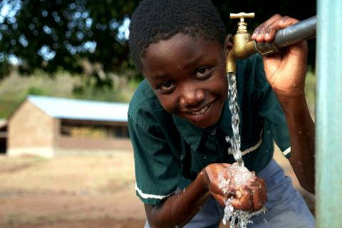 A learner at Nankhwali Primary School smiles as he opens a tap to drink safe and clean water