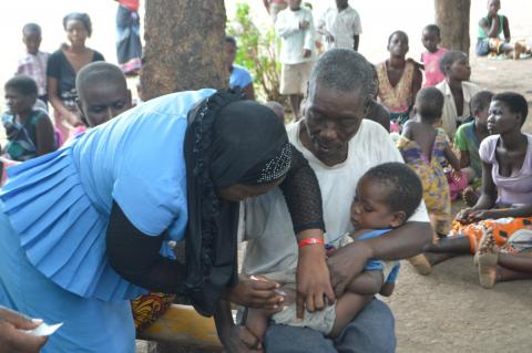Three-year-old Patrick, in his grandfather's arms, gets his measles-rubella vaccine at Nkhwazi camp in Chikwawa
