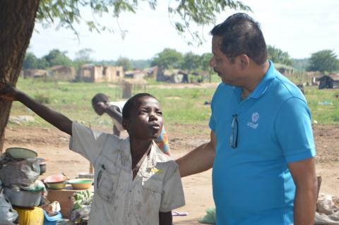 Malawi Education Programme Manager Vinobajee Gautam speaks to 12  -  year  -  old   Yohane Gasiano at Mwalija camp in Chikwawa