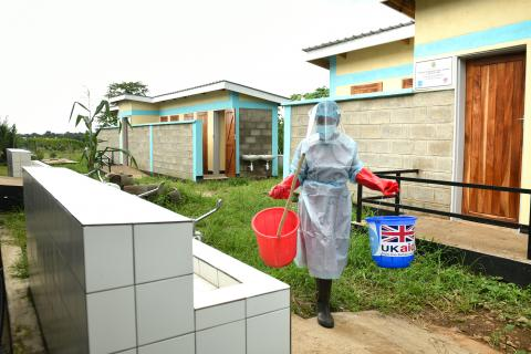 Cleaner Rose Kajawo carrying buckets of water as she prepares to start cleaning. Behind her are the toilet blocks constructed by UNICEF with support from UK Aid