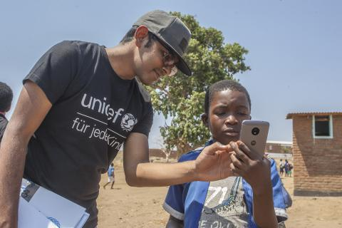 A UNICEF official from Germany teaches twelve year old Innocent Katiya, one of the Standard eight learners at Nankhali Primary School in Lilongwe how to take pictures on a mobile phone during the tour of construction works at the school