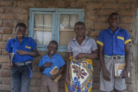 Besina Phingo, a single mother of four, and a Social Cash Transfer Programme (SCTP) beneficiary poses with her children, Christopher Jerald, 16, who has just sat for the Primary School Leaving Certificate Examinations, right, Anderson Mphambo, eight years old and in Standard three,near left, and Chikondi Mphambo, 13, who is in Standard Four, far left, at their home Kunyungwi Village, Sub Traditional Authority Tsikulamowa soon after coming back from receiving her monthly cash lot of Social Cash Transfer Prog