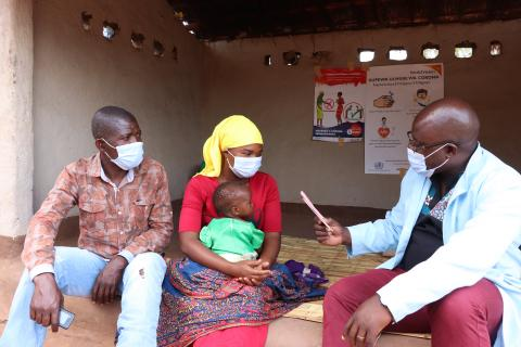 A family interacts with a health worker during a growth monitoring session during growth monitoring sessions