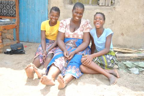 Matilda and her two twin daughters – Yankho and Pemphero. Behind them on the chair is some of their learning materials