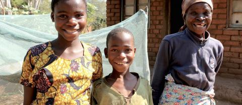 Meria Maulana and her grandchildren Estere and Francis stand cheerfully outside their home in Balaka, Malawi