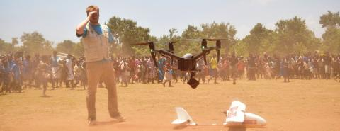 A UNICEF staff member watches a drone land at Maganga Primary School in Salima