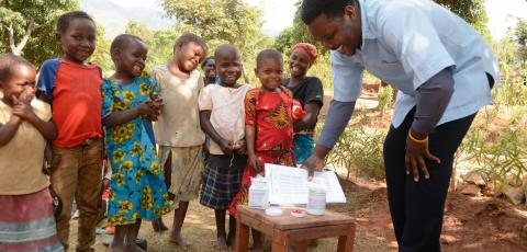 A health officer giving children in Mangumba Village in Zomba,  vitamin A and albendazol during child health days