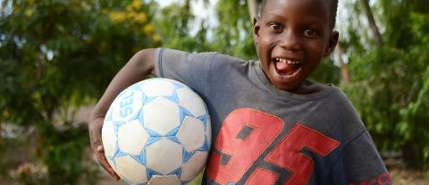A little boy plays with a football at Kubwera Kwa Yesu Childrens Corner in Mulanje.