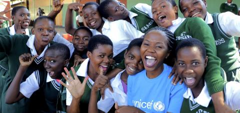 Students at St. Monica Secondary School in Mangochi pose for a photo with a UNICEF staff member.