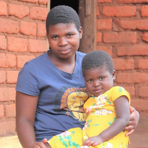 Enifa sits outside her home with her daughter who she got pregnant with at 14-years old