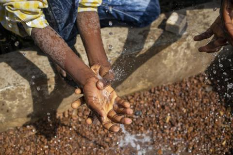 A primary school student washing his hands at a tap installed by UNICEF.