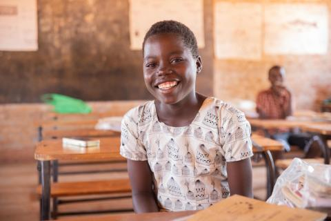A student smiling in class at Chipelera Primary School