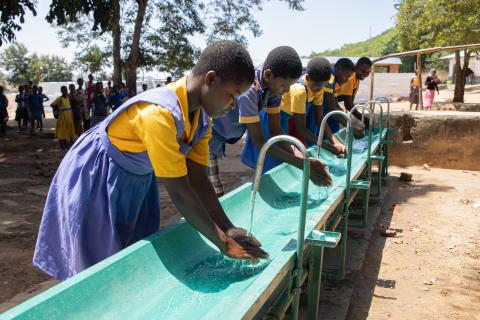 Children washing hands at a handwashing station provided by UNICEF