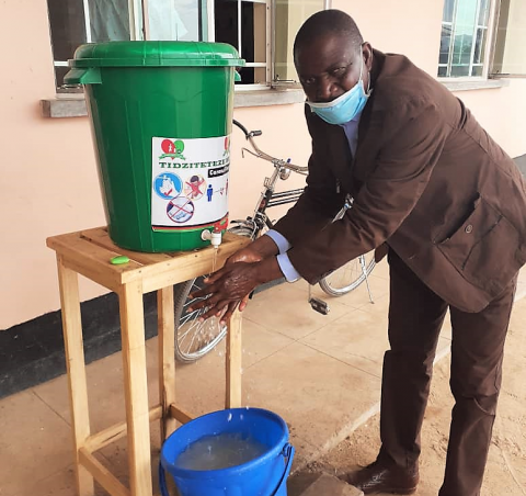 Senior Chief Kawinga of Machinga district, washing his hands before entering his headquarters office
