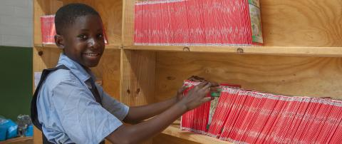 Eliza Kamanga choosing book on library shelf