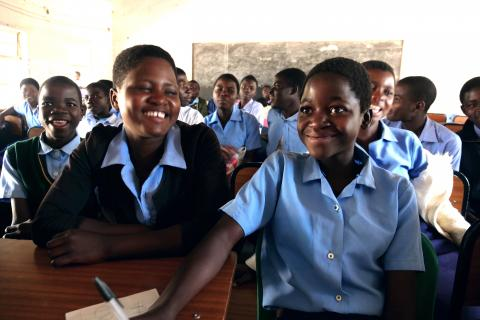 Form 2 students smiles as they follow a lesson in class at Mdeka community secondary school in Blantyre rural