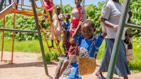 Children playing on the swings at Makhankula CBCC in Dedza