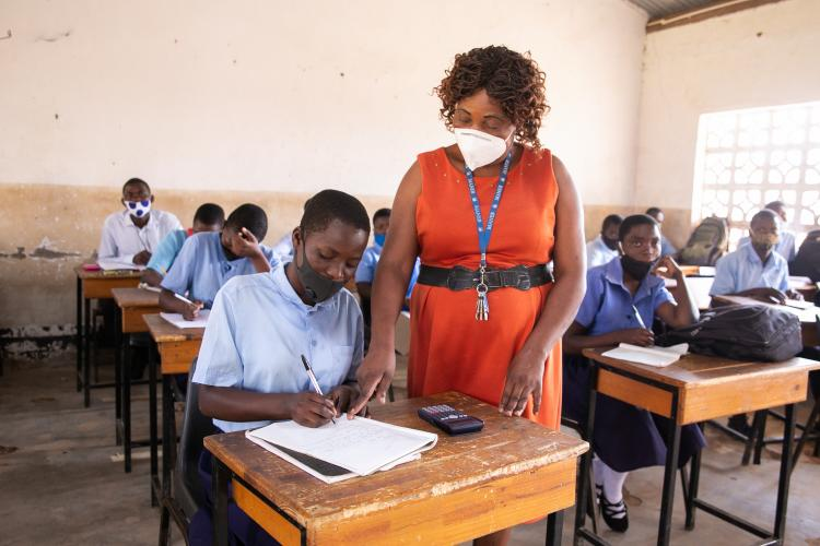 A teacher at Mpamba Community Day Secondary School helping a student in class