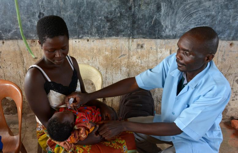 A health worker vaccinating a child at the mobile clinic