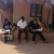 Brighton Ndambo in black attire, conducting an interview with an SCTP beneficiary family in Balaka