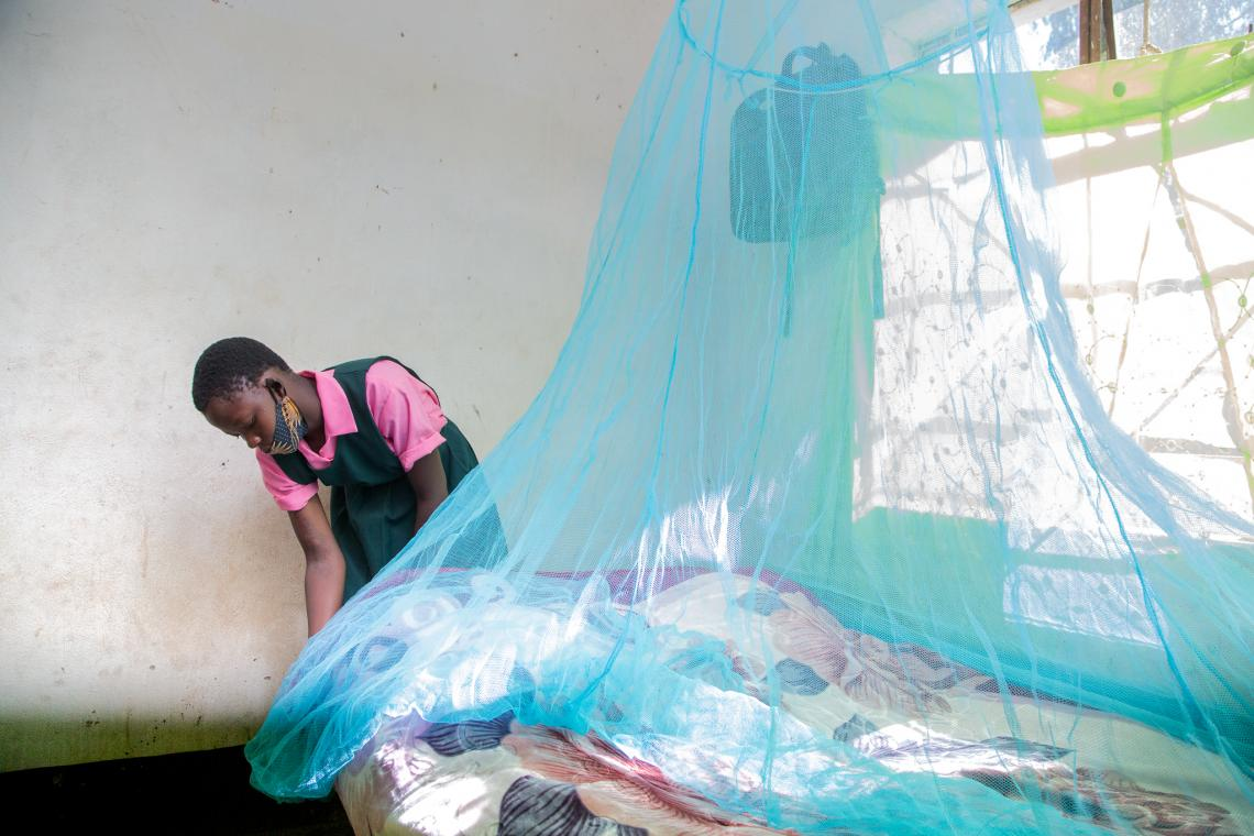 Mercy Mwanza, a learner from Mphasi Primary School tucks in her new mosquito net at home in Mphasi Village in Kasungu