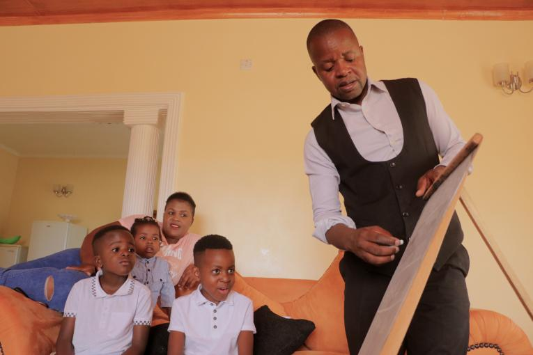 "One of UNICEF's ""Super Dads', Davis Njobvu interacting with his children at home."