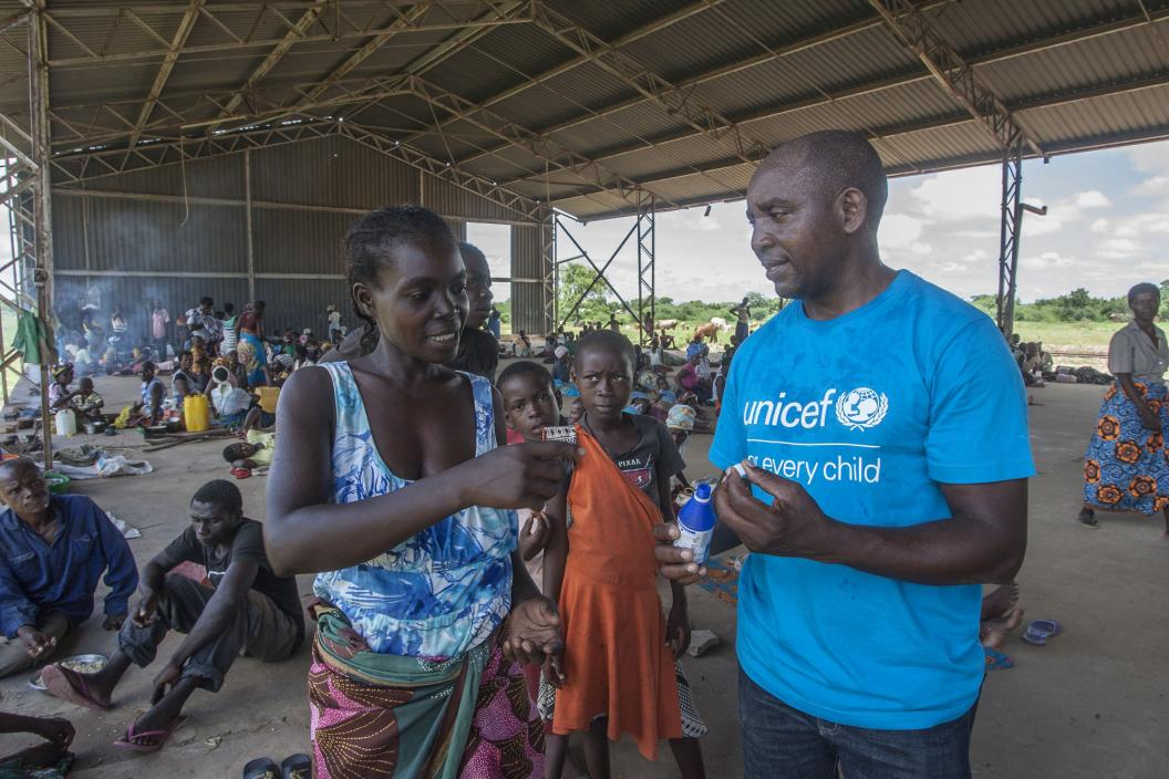 UNICEF WASH Officer Alan Kumwenda shows Annie Joseph how to use water guard at Bangula Admarc Camp in Nsanje.