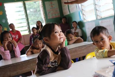 Girl stares ahead with head on palm in classroom