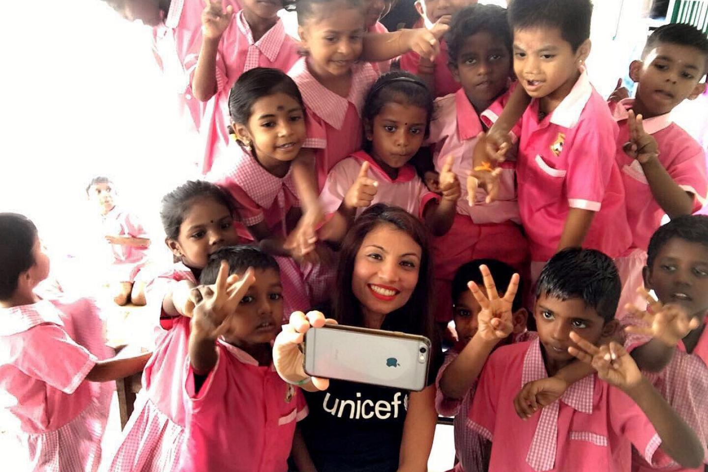 UNICEF staff and children take a wefie