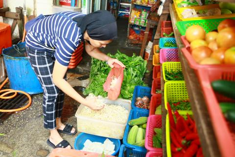 Lady selecting vegetables at sundry shop