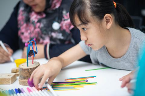A child at a consultation with children with disabilities selects a pen for her assignment