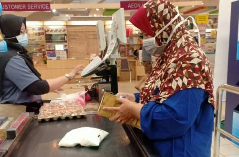 Woman paying for groceries at supermarket