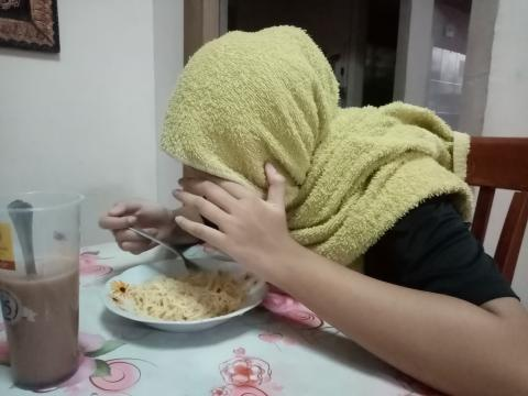 Woman hiding her face eating noodles