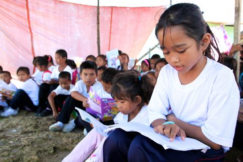 girls and boys reading in tent