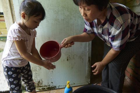 mother helps girl child wash her hands