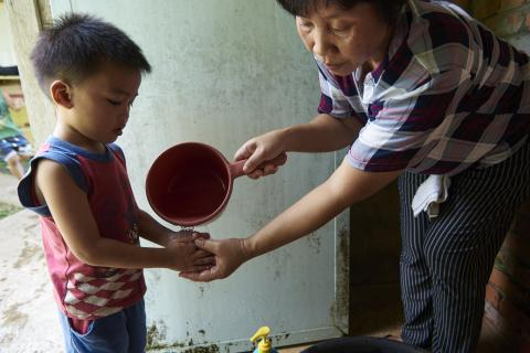 Mother helping to wash hands of boy child
