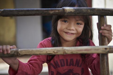 A Malaysian child smiles behind a wood fence