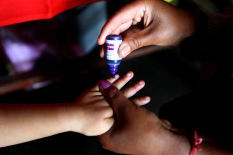 child hand receiving vaccine from adult hands
