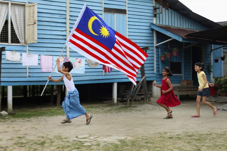 Children running with Malaysia flag
